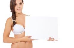 Muchacha en la ropa interior que lleva a cabo la muestra blanca Fotografía de archivo