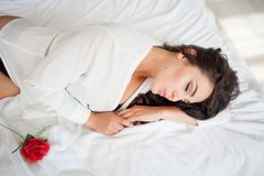 Muchacha en la ropa interior que miente en una cama con una rosa fotografía de archivo libre de regalías