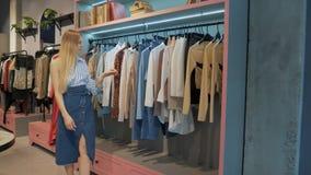 Muchacha en la sala de exposición de la tienda de ropa metrajes