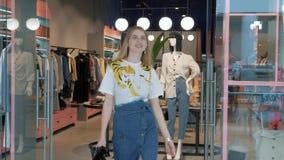 Muchacha en la sala de exposición de la tienda de ropa almacen de video