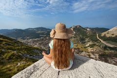 Muchacha en la sentada del top de la montaña y admirar la visión fotos de archivo