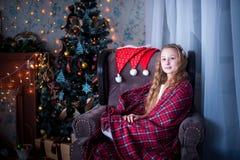 Muchacha en la silla envuelta en una manta, fondo del árbol de navidad Fotografía de archivo