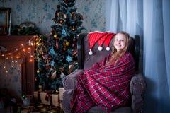 Muchacha en la silla envuelta en una manta, fondo del árbol de navidad Fotos de archivo