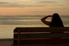 Muchacha en la silueta que mira puesta del sol Imagen de archivo libre de regalías