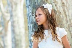 Muchacha en la situación blanca al lado del árbol. Fotografía de archivo