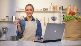 Muchacha en la tarjeta de banco de la tenencia de la cocina, satisfecha con la compra de la comida sobre Internet almacen de video