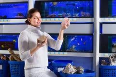 Muchacha en la tienda del acuario que elige piedras, rocas y el co interesantes Imagen de archivo
