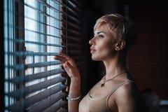 Muchacha en la ventana con la persiana Fotografía de archivo libre de regalías