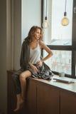 Muchacha en la ventana con una taza de café y de revista Fotos de archivo libres de regalías