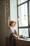 Muchacha en la ventana con una taza de café y de revista Imagen de archivo