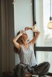 Muchacha en la ventana con una taza de café y de revista Foto de archivo libre de regalías