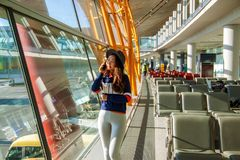 Muchacha en la ventana del aeropuerto que habla por el tel?fono fotos de archivo libres de regalías