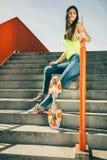 Muchacha en las escaleras con el monopatín Foto de archivo libre de regalías