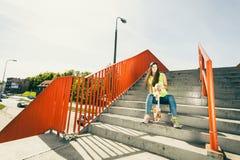 Muchacha en las escaleras con el monopatín Imagen de archivo libre de regalías