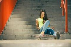 Muchacha en las escaleras con el monopatín Foto de archivo