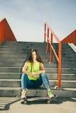 Muchacha en las escaleras con el monopatín Imagenes de archivo