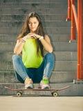 Muchacha en las escaleras con el monopatín Imagen de archivo