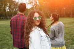 Muchacha en las gafas de sol que llevan la chaqueta que se coloca al aire libre Foto de archivo