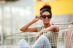 Muchacha en las gafas de sol que se sientan dentro de una carretilla de las compras al aire libre Fotografía de archivo