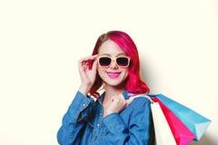 Muchacha en las gafas de sol sosteniendo los panieres coloreados imagen de archivo libre de regalías