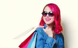 Muchacha en las gafas de sol sosteniendo los panieres coloreados foto de archivo libre de regalías