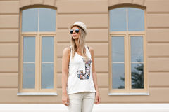 Muchacha en las gafas de sol y el sombrero que se colocan cerca de la casa Foto de archivo