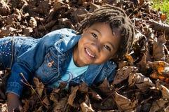 Muchacha en las hojas Foto de archivo libre de regalías