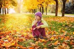 Muchacha en las hojas de otoño en el parque en el aire fresco Foto de archivo libre de regalías