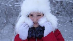 Muchacha en las sonrisas mullidas blancas del sombrero en día escarchado frío Días de fiesta de la Navidad Primer metrajes