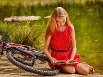 Muchacha en libro de lectura de ciclo cerca de la bicicleta en el parque al aire libre foto de archivo libre de regalías