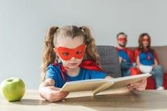 muchacha en libro de lectura del traje del super héroe mientras que padres estupendos fotos de archivo libres de regalías