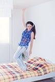 Muchacha en los auriculares que bailan en la cama Imagen de archivo libre de regalías