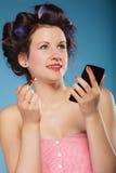 Muchacha en los bigudíes de pelo que aplican el lápiz labial rojo Imagen de archivo libre de regalías