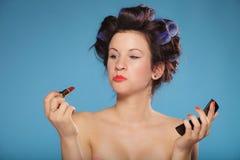 Muchacha en los bigudíes de pelo que aplican el lápiz labial rojo Fotos de archivo libres de regalías