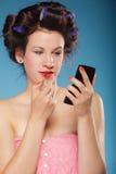 Muchacha en los bigudíes de pelo que aplican el lápiz labial rojo Fotos de archivo