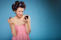 Muchacha en los bigudíes de pelo que aplican el lápiz labial rojo Fotografía de archivo libre de regalías