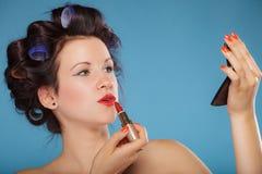 Muchacha en los bigudíes de pelo que aplican el lápiz labial rojo Fotografía de archivo