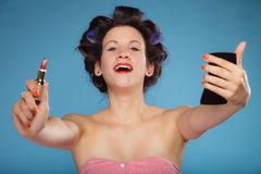 Muchacha en los bigudíes de pelo que aplican el lápiz labial rojo Imagen de archivo