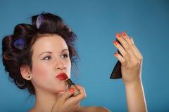 Muchacha en los bigudíes de pelo que aplican el lápiz labial rojo Imágenes de archivo libres de regalías