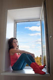 Muchacha en los cargadores del programa inicial rojos que se sientan en un windowsill Imagen de archivo libre de regalías