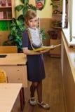 Muchacha en los escritorios de la escuela Imagen de archivo libre de regalías