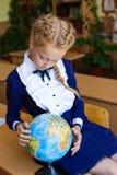Muchacha en los escritorios de la escuela Fotos de archivo