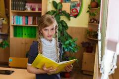 Muchacha en los escritorios de la escuela Imagen de archivo