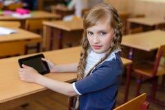 Muchacha en los escritorios de la escuela Foto de archivo libre de regalías
