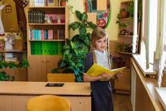 Muchacha en los escritorios de la escuela Fotografía de archivo libre de regalías