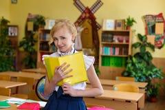 Muchacha en los escritorios de la escuela Foto de archivo