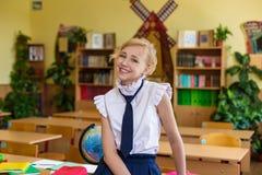 Muchacha en los escritorios de la escuela Imágenes de archivo libres de regalías