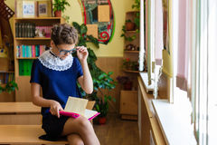 Muchacha en los escritorios de la escuela Fotografía de archivo