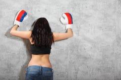 Muchacha en los guantes de boxeo inclinados a la pared Foto de archivo