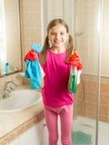Muchacha en los guantes de goma que limpian el cuarto de baño con el paño y el espray Imagenes de archivo